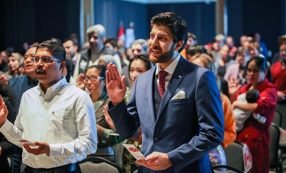 """<span class=""""caption"""">New immigrants to Canada, including Syrian-born Tareq Hadhad (centre) who founded the company Peace by Chocolate in Antigonish, N.S., swear allegiance at an Oath of Citizenship ceremony in Halifax in January 2020. </span> <span class=""""attribution""""><span class=""""source"""">THE CANADIAN PRESS/Riley Smith </span></span>"""