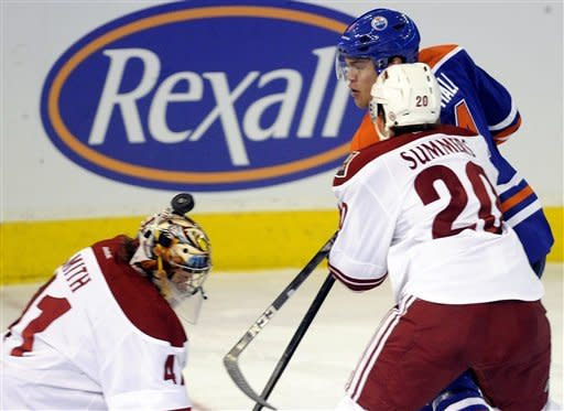 Edmonton Oilers' Taylor Hall, center, bounces the puck off of the head of Phoenix Coyotes goalie Mike Smith, as Chris Summers (20) defends during the first period of an NHL hockey game in Edmonton, Alberta, on Saturday, Feb. 25, 2012. (AP Photo/The Canadian Press, John Ulan)