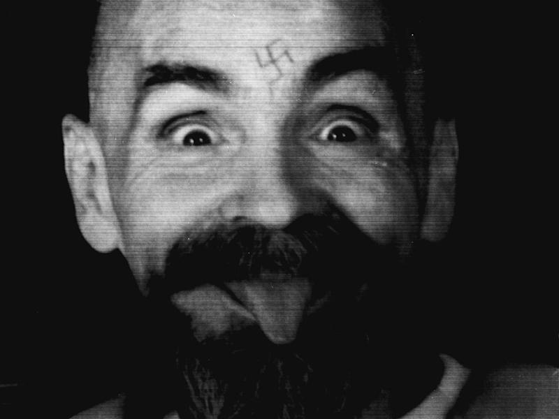 Charles Manson clowns around as he is led to his cell in 1989: Reuters