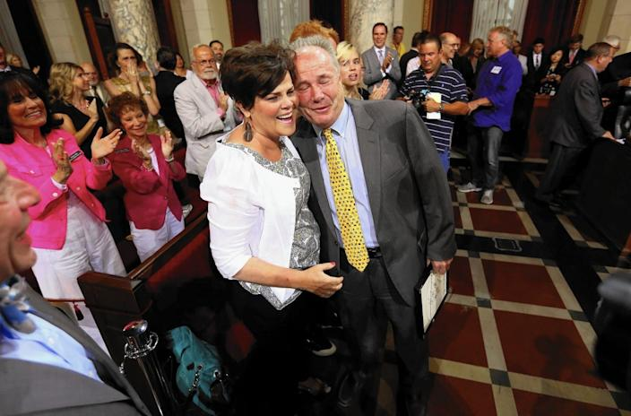 City Councilman Tom LaBonge hugs his wife, Brigid, in 2015 while several people standing behind them applaud in a room.