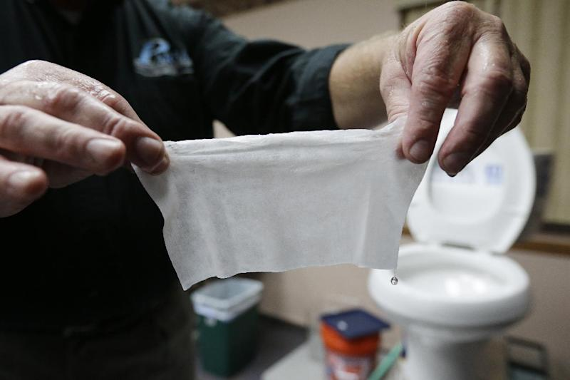 In this photograph taken, Friday, Sept. 20, 2013, in Middlesex, N.J., Rob Villee, executive director of the Plainfield Area Regional Sewer Authority in New Jersey, holds up a wipe he flushed through his test toilet in his office. Increasingly popular bathroom wipes, thick, premoistened towelettes that are advertised as flushable, are creating clogs and backups in sewer systems around the nation. The problem has gotten so bad in this upstate New York town that frustrated sewer officials traced the wipes back to specific neighborhoods, and even knocked on doors to break the embarrassing news to residents that they are the source of a costly, unmentionable mess. An industry trade group this month revised its guidelines on which wipes can be flushed, and has come out with a universal stick-figure, do-not-flush symbol to put on packaging. (AP Photo/Julio Cortez)