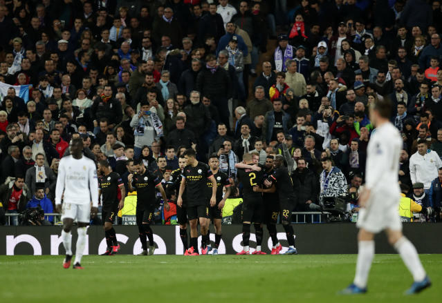 Manchester City's Kevin De Bruyne celebrates with teammates after scores his side's second goal from the penalty spot during the Champions League, round of 16, first leg soccer match between Real Madrid and Manchester City at the Santiago Bernabeu stadium in Madrid, Spain, Wednesday, Feb. 26, 2020. (AP Photo/Manu Fernandez)