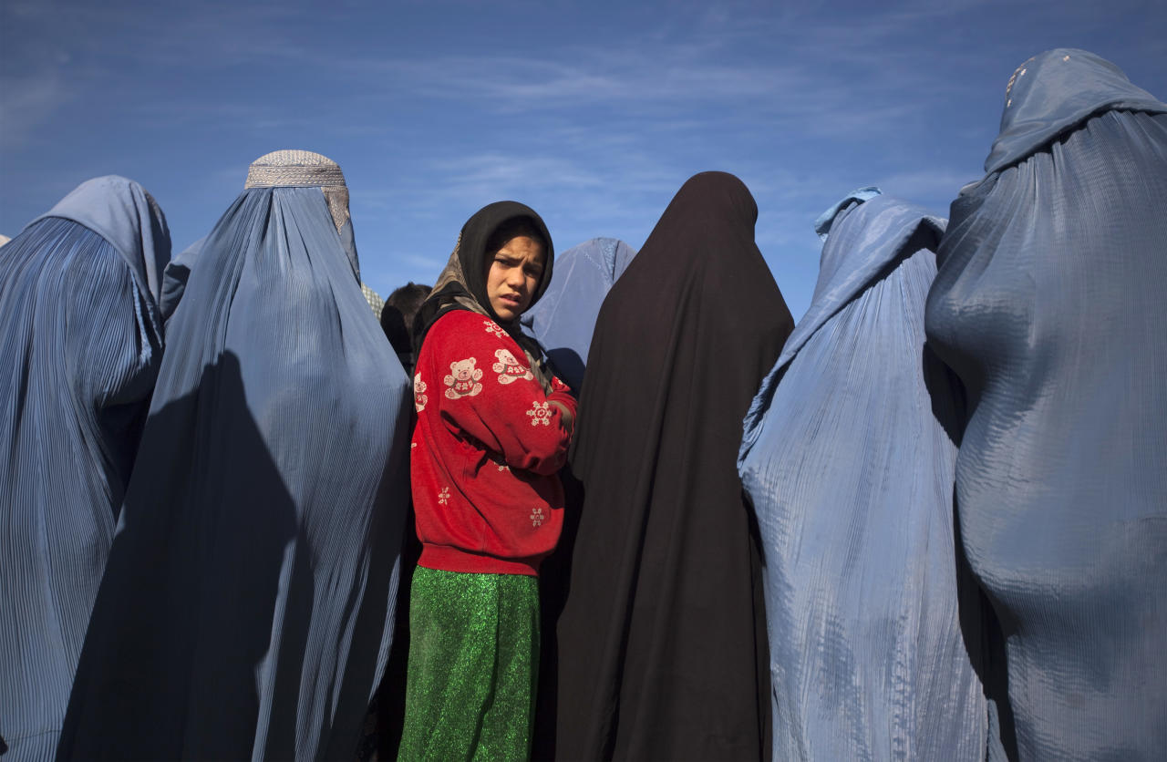 An Afghan girl stands among widows clad in burqas during a cash for work project by humanitarian organisation CARE International in Kabul January 6, 2010. In this project, 500 Afghan widows, most of whom lost their husbands during the civil wars in Afghanistan, make blankets after receiving the materials from CARE. REUTERS/Ahmad Masood (AFGHANISTAN - Tags: SOCIETY)