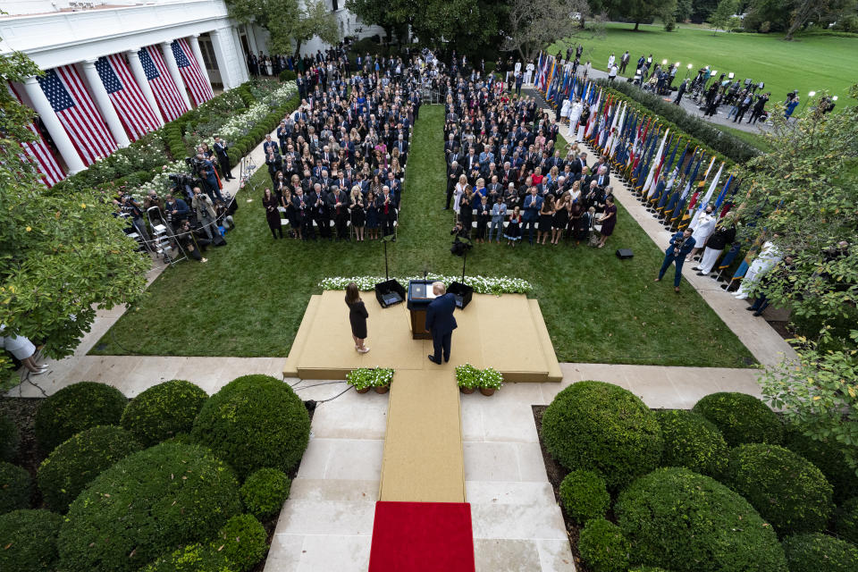 In this Sept. 26, 2020, photo President Donald Trump, center, stands with Judge Amy Coney Barrett as they arrive for a news conference to announce Barrett as his nominee to the Supreme Court, in the Rose Garden at the White House in Washington. Former New Jersey Gov. Chris Christie watches from fourth row from front on far right. (AP Photo/Alex Brandon)