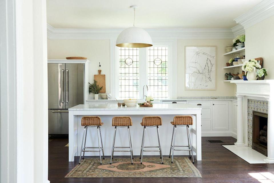"<p>Take note from this space designed by <a href=""https://leanneford.com/"" rel=""nofollow noopener"" target=""_blank"" data-ylk=""slk:Leanne Ford Interiors"" class=""link rapid-noclick-resp"">Leanne Ford Interiors</a> and paint your kitchen a subtly sunny hue, like buttercream yellow. Then lay down an area rug with pops of coral for a fresh, bold anchor. The large drum pendant in white and gold speaks to the pretty paint color, too. Delicate and delightful.</p>"