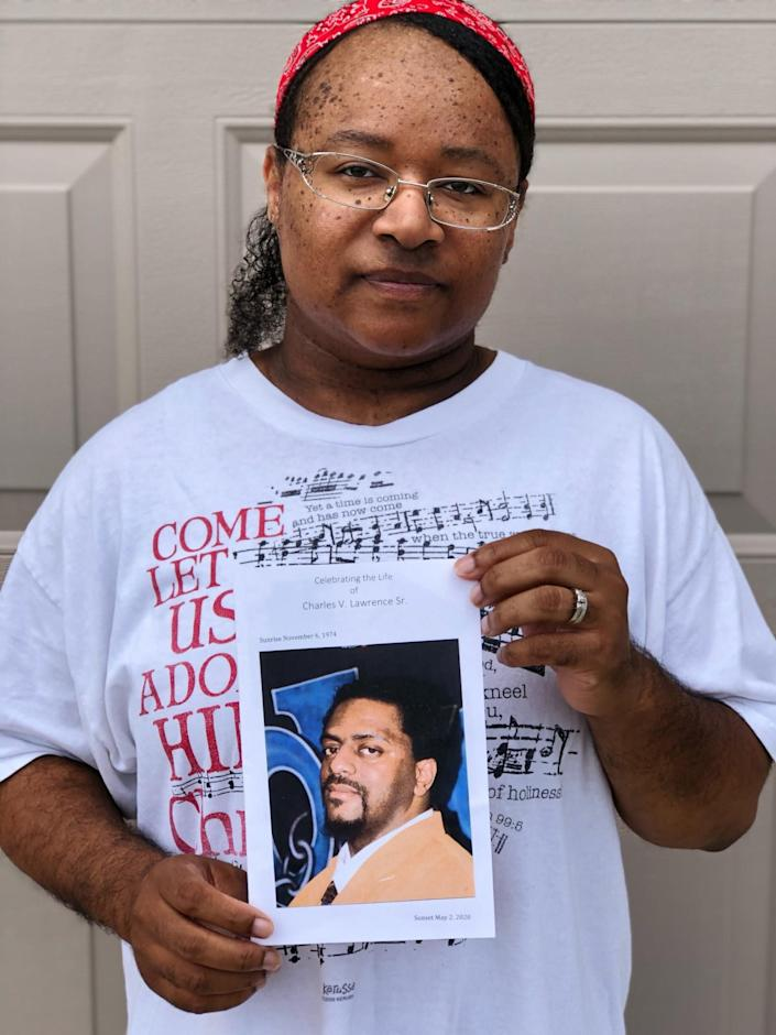 Sanya Lawrence holds a photo of her husband, Charles Lawrence, who died from the coronavirus in May 2020. (Photo: Courtesy of Sanya Lawrence)
