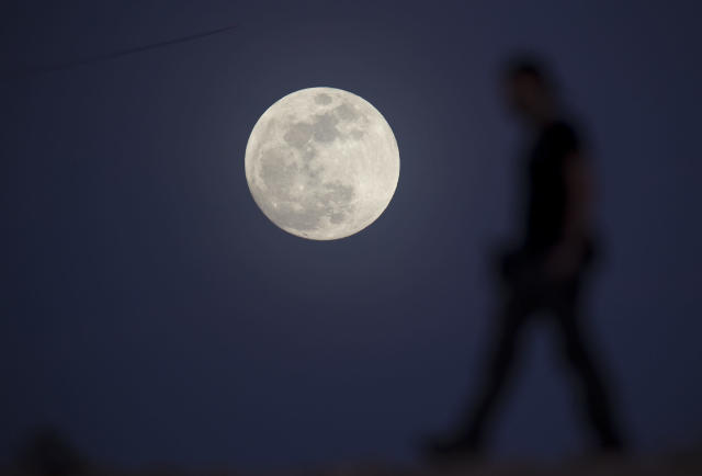 <p>Ultimate Fighter Championship videographer Chris Warner walks past the moon as he films b-roll in Las Vegas on Tuesday, Jan 30, 2018. (Photo: Richard Brian/Las Vegas Review-Journal via AP) </p>