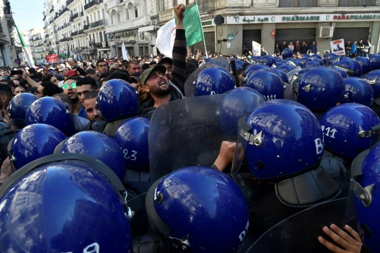 Algerian riot police block the progress of an anti-government demonstration heading towards the presidential palace in the capital Algiers, on Saturday