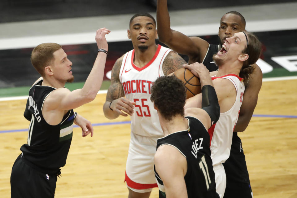 Houston Rockets' Kelly Olynyk, right, gets fouled by Milwaukee Bucks' Brook Lopez (11) during the first half of an NBA basketball game Friday, May 7, 2021, in Milwaukee. (AP Photo/Aaron Gash)