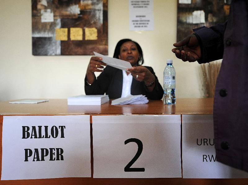 A poll clerk hands ballot papers to a registered Rwandan voter at a polling station on December 17, 2015 at the Rwandan High Commission in Nairobi (AFP Photo/Tony Karumba)