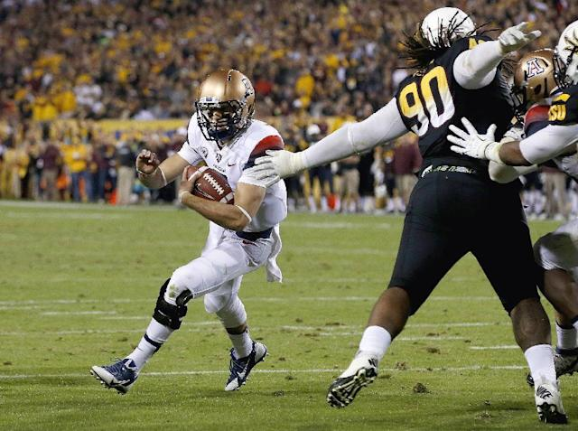 Arizona's B.J. Denker, left, gets past Arizona State's Will Sutton (90) for a touchdown during the first half of an NCAA college football game Saturday, Nov. 30, 2013, in Tempe, Ariz. (AP Photo/Ross D. Franklin)