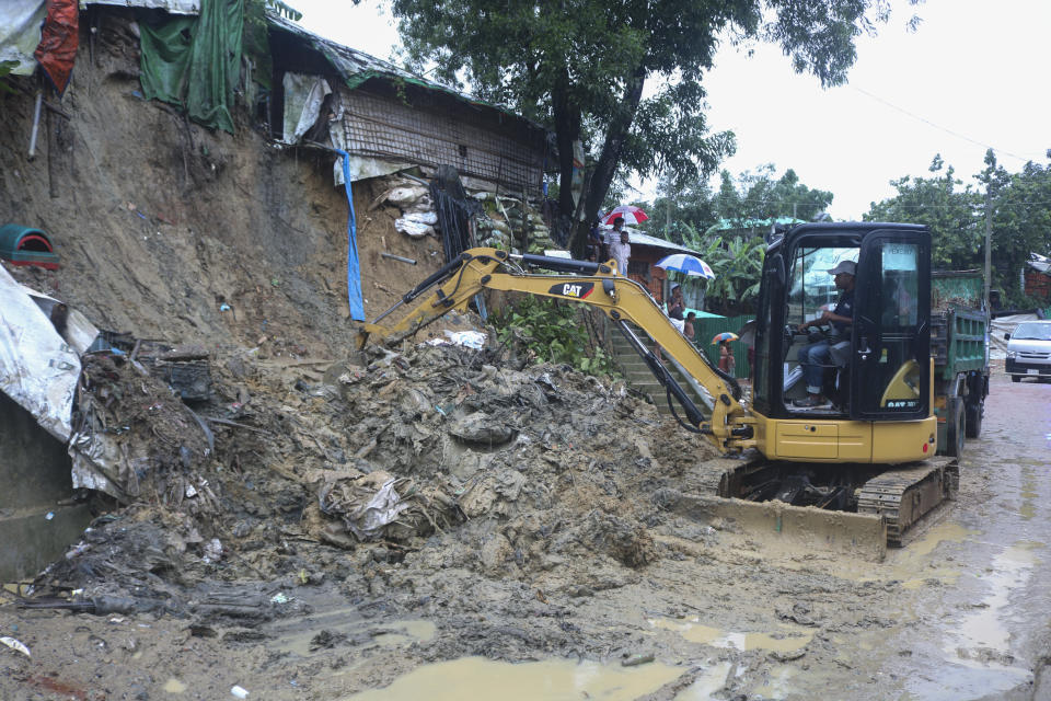 Rohingya refugees and others look on as machinery is used to remove debris after a landslide triggered by heavy rains in a camp at Ukhiya in Cox's Bazar district, Bangladesh, Tuesday, July 27, 2021. (AP Photo/ Shafiqur Rahman)