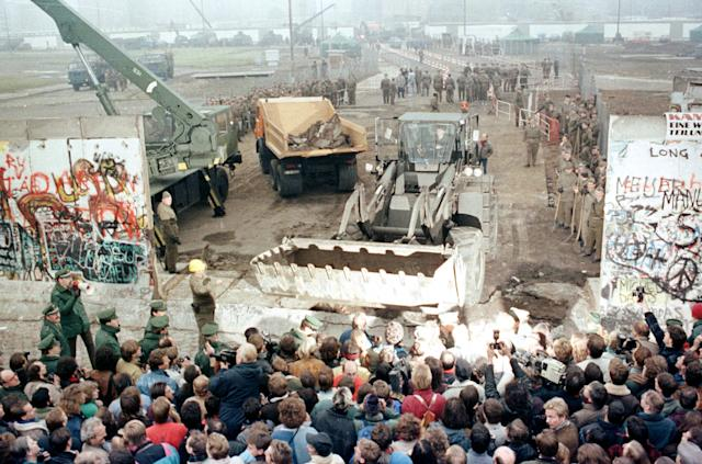 An East German bulldozer and crane knock down the Berlin Wall at Potsdamer Platz to make way for a new border crossing on Nov. 12, 1989. (Photo: Wolfgang Rattay/Reuters)