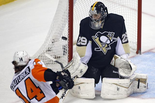 Pittsburgh Penguins goalie Marc-Andre Fleury (29) blocks a shot by Philadelphia Flyers' Sean Couturier (14) in the first period of an NHL hockey game in Pittsburgh, Saturday, April 12, 2014. (AP Photo/Gene J. Puskar)