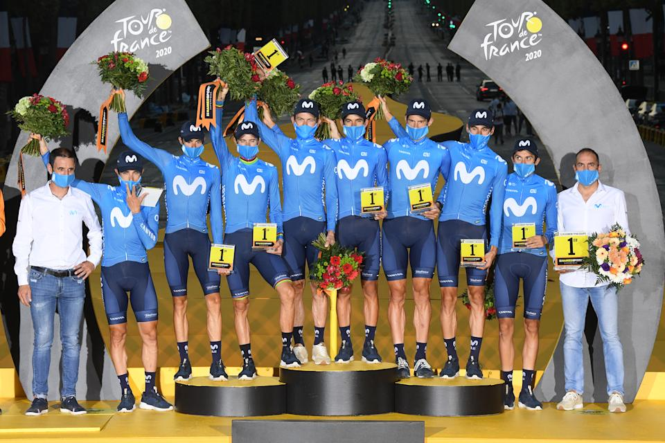 PARIS, FRANCE - SEPTEMBER 20: Podium / Dario Cataldo of Italy, Imanol Erviti of Spain, Enric Mas Nicolau of Spain, Nelson Oliveira of Portugal, Jose Joaquin Rojas Gil of Spain, Marc Soler Gimenez of Spain, Alejandro Valverde Belmonte of Spain, Carlos Verona Quintanilla of Spain and Movistar Team / Jose Luis Arrieta of Spain Sports director of Movistar Team / Pablo Lastras of Spain Sports director of Movistar Team / Best Team / Celebration / Trophy / Flowers / Mask / Covid safety measures / during the 107th Tour de France 2020, Stage 21 a 122km stage from Mantes-La-Jolie to Paris Champs-Élysées / #TDF2020 / @LeTour / on September 20, 2020 in Paris, France. (Photo by Stephan Mantey - Pool/Getty Images)