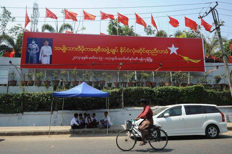 A Myanmar man rides a bicycle past a billboard announcing the congress of the National League for Democracy at the Royal Rose Hall in Yangon on March 8, 2013. Myanmar's Aung San Suu Kyi was set to address her party during its historic congress Saturday as the once-banned opposition seeks to revamp its leadership and eyes its first chance at power in 2015 polls