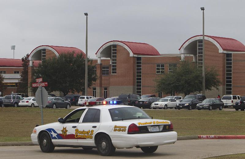 A police vehicle is parked near the entrance of North Shore High School after a shooting occurred Wednesday, Dec. 5, 2012, in Houston. Police say a high school student taken into custody after he sent a text message to a friend saying he wanted to hurt himself shot himself with a hidden gun while handcuffed inside a patrol car. Authorities on Thursday said deputies did not conduct a complete search of the student, and failed to find the hidden gun. (AP Photo/Houston Chronicle, Cody Duty) MANDATORY CREDIT