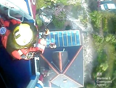 A helicopter crew rescue a stranded couple from a flooded house in Coverack in Cornwall,