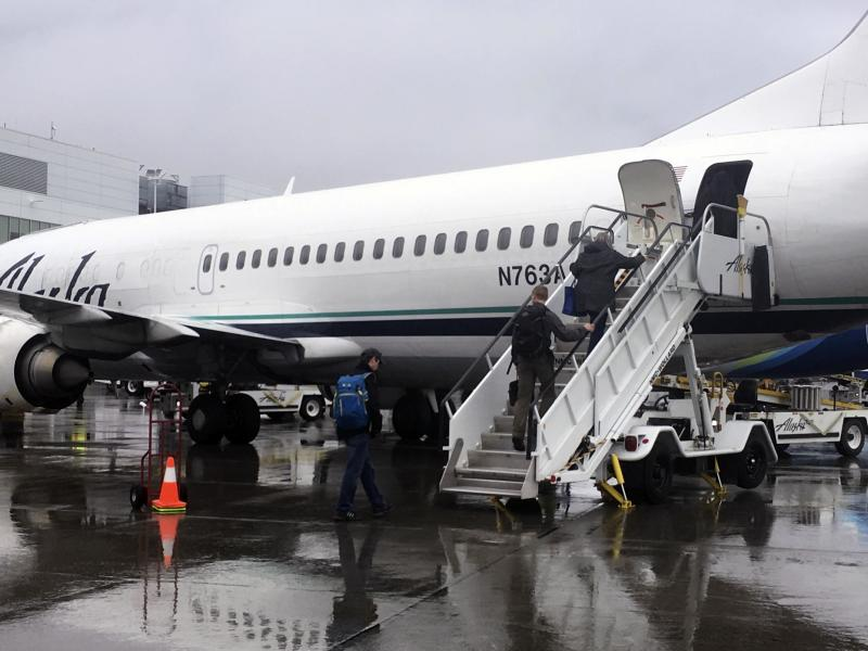 In this photo taken Friday, Sept. 22, 2017, passengers board an Alaska Airlines jet from the rear using stairs at Ted Stevens Anchorage International Airport in Anchorage, Alaska. The airline is retiring its combi planes, Boeing 737-400s designed to be half cargo immediately behind the cockpit and then seating for 72 passengers in the rear. (AP Photo/Mark Thiessen)