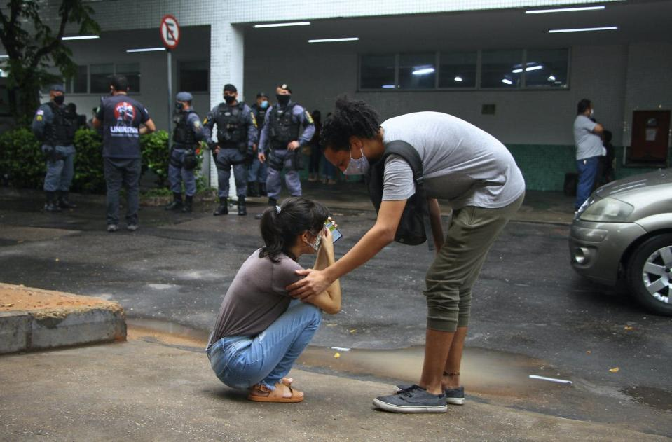 Woman is on knees crying outside of a building, a masked woman comforts her