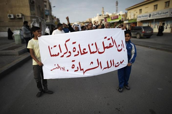 Bahraini protesters hold a banner during a protest in the village of Jidhafs, west of Manama, against the execution of prominent Shiite Muslim cleric Nimr al-Nimr by Saudi authorities, on January 2, 2016 (AFP Photo/Mohammed Al-Shaikh)