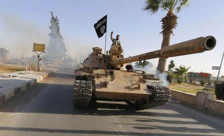 Militant Islamist fighters on a tank take part in a military parade along the streets of northern Raqqa province