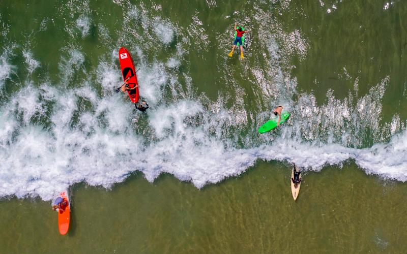 Surfers and paddleboarders enjoy the Pacific coast - AFP