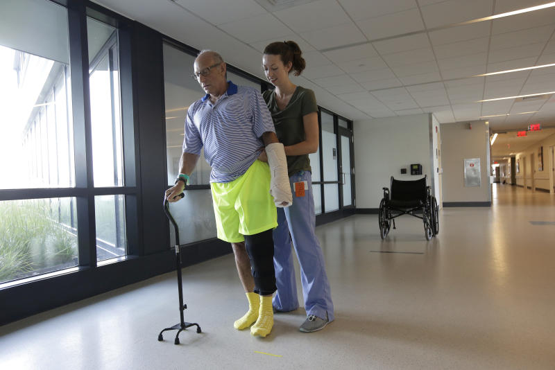 William Lytton, of Scarsdale, N.Y., left, is assisted by physical therapist Caitlin Geary at Spaulding Rehabilitation Hospital, in Boston, Tuesday, Aug. 28, 2018, while recovering from a shark attack. Lytton suffered deep puncture wounds to his leg and torso after being attacked by a shark on Aug. 15 while swimming off a beach, in Truro, Mass. Lytton injured a tendon in his arm while fighting off the shark. (AP Photo/Steven Senne)