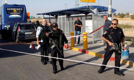 Israeli policemen stand guard at the scene of a Palestinian ramming attack at the Gush Etzion Junction, south of the West Bank city of Bethlehem