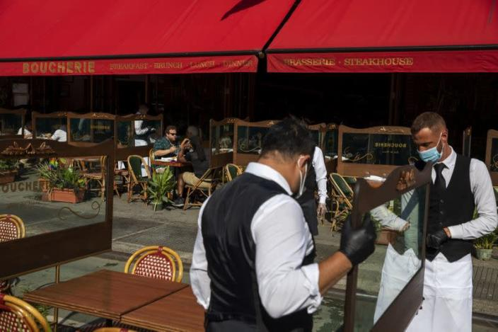 Waiters at a restaurant adjust social distancing screens outside for outdoor seating a restaurant in New York City
