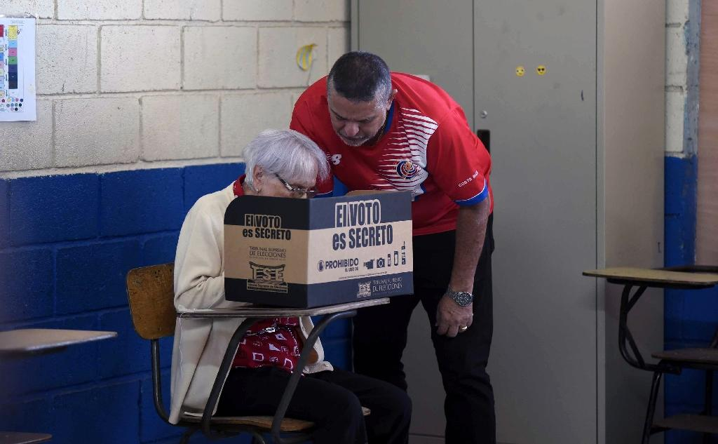 Mario Alfaro (R) assists his 85-year-old mother Maruja to cast her vote, at a polling station in San Jose, during Costa Rica's national election, in which gay marriage is a central issue (AFP Photo/CARLOS GONZALEZ CARBALLO)