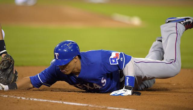 Texas Rangers' Leonys Martin dives back to first under the tag of Los Angeles Angels first baseman Efren Navarro during the eighth inning of a baseball game, Saturday, June 21, 2014, in Anaheim, Calif. (AP Photo/Mark J. Terrill)