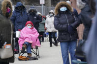 Judy McKim, center left, waits in line with others for the COVID-19 vaccine in Paterson, N.J., Thursday, Jan. 21, 2021. The first people arrived around 2:30 a.m. for the chance to be vaccinated at one of the few sites that does not require an appointment. (AP Photo/Seth Wenig)