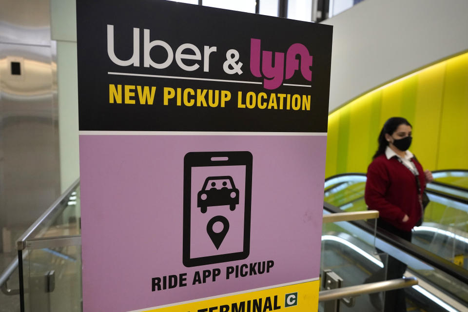 FILE - In this Feb. 9, 2021 file photo, a passer-by walks past a sign offering directions to an Uber and Lyft ride pickup location at Logan International Airport, in Boston.  Uber and Lyft have teamed up to create a database of drivers ousted from their ride-hailing services for complaints about sexual assault and other crimes that have raised passenger-safety concerns for years. The clearinghouse unveiled Thursday, March 11,  will initially list drivers expelled by the ride-hailing rivals in the U.S. But it will also be open to other companies that deploy workers to perform services such as delivering groceries or take-out orders from restaurants(AP Photo/Steven Senne, File)