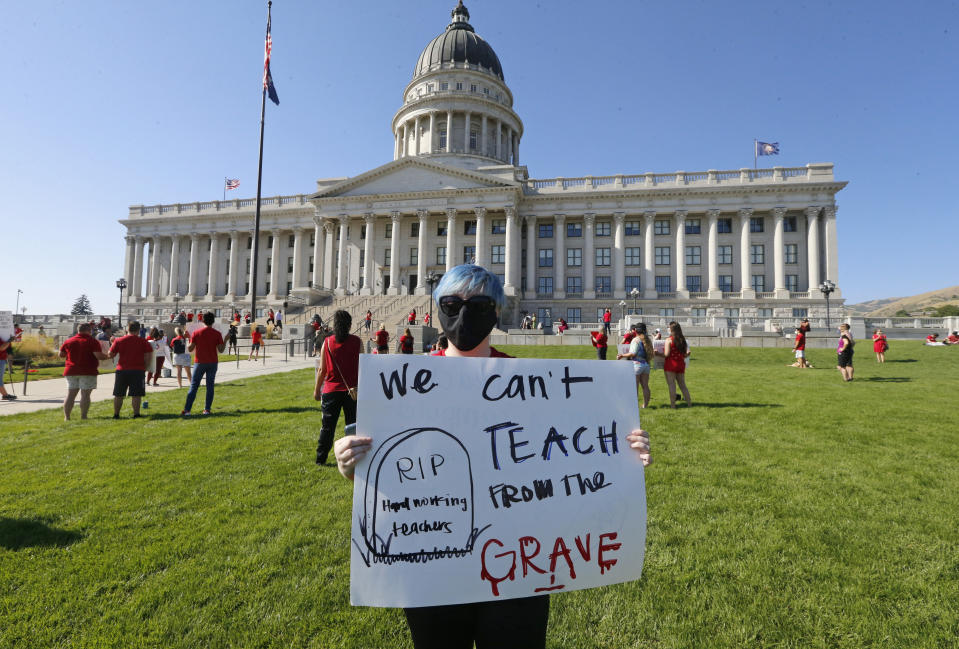 Utah school teacher Brittany Goddard protests at the Utah State Capitol, Friday, Aug. 7, 2020, in Salt Lake City. The Utah Board of Education has rejected multiple proposals requiring stricter precautions against the coronavirus as schools reopen across the state. The board voted 9-5 Thursday against a series of mandates, including one that would limit the number of students in a classroom if community spread spikes above the 5% reopening threshold set by the World Health Organization, the Deseret News reported. (AP Photo/Rick Bowmer)