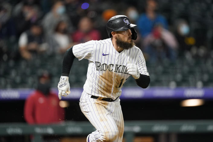 Colorado Rockies' Chris Owings follows the flight of his RBI-double off Arizona Diamondbacks starting pitcher Madison Bumgarner in the fourth inning of a baseball game Wednesday, April 7, 2021, in Denver. (AP Photo/David Zalubowski)
