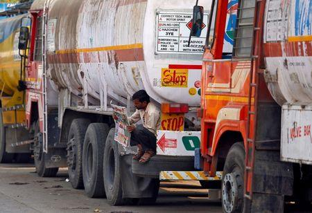 A driver reads a newspaper as he sits on a spare tire attached to a parked oil tanker at a truck terminal in Mumbai