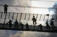 Workers are silhouetted against the sky during a ceremony marking 100 years of diplomatic relations between Japan and Romania, at the construction site of a suspension bridge over the Dnube river in Braila, Romania, Thursday, Aug. 26, 2021. The bridge, built by Japanese and Italian companies, with a span of 1,974.3 meters, will be the largest of its kind in Romania and the third in the European union.(AP Photo/Vadim Ghirda)