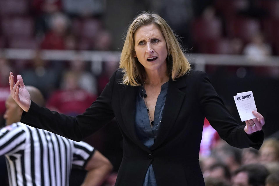 FILE - In this Saturday, Dec. 28, 2019 file photo, UC Davis head coach Jennifer Gross looks for a foul call during the second half of an NCAA college basketball game against Stanford in Stanford, Calif. For all the stops and starts endured by men's and women's college basketball teams because of the pandemic, more than 80% of scheduled conference games were played this season, according to research by The Associated Press. The season was nonetheless a grind for most teams and none had it harder than the George Washington men and UC Davis women. By Eric Olson. (AP Photo/Tony Avelar, File)
