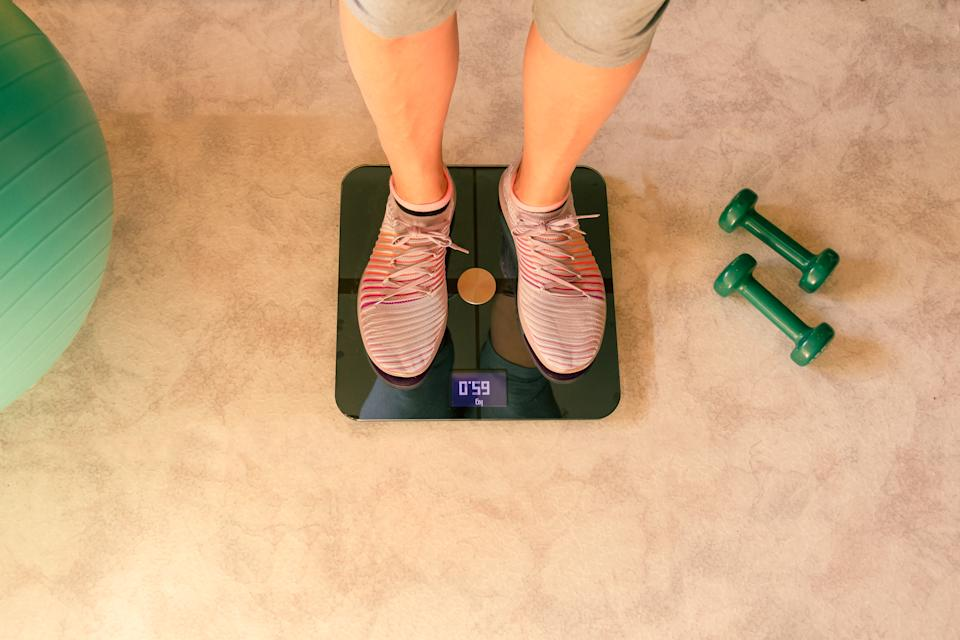woman's feet being weighed on a scale at home. home training concept. Quarantine concept