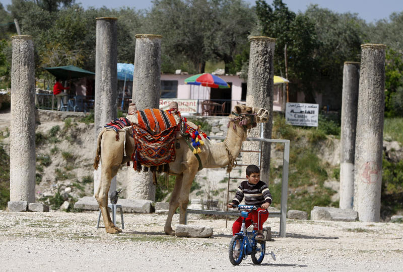 In this Saturday, April 6, 2013 photo, a Palestinian child rides a bicycle near the Roman basilica and forum in the village of Sebastia near the West Bank city of Nablus. The ancient town of Sebastia is one of the greatest archaeological sites of the Holy Land, attracting tourists and pilgrims over the centuries with its overlapping layers of history dating back 3,000 years. But visitors who come to the site today will find it in a state of neglect. (AP Photo/Majdi Mohammed)