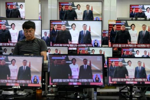 South Korean President Moon Jae-in (right on screens) met three times with the North's leader Kim Jong Un last year