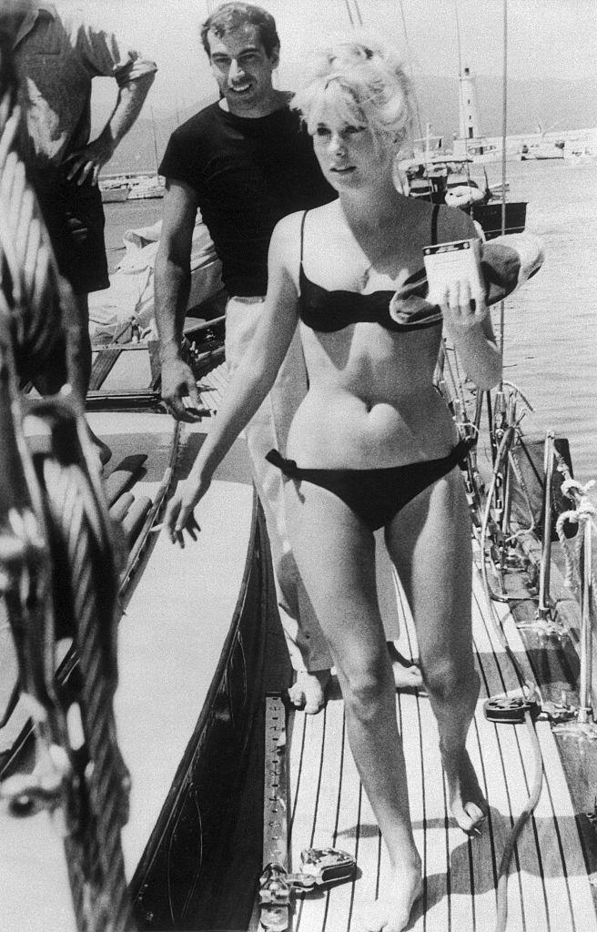 <p>French film star Catherine Deneuve relaxes aboard a sailboat with director Roger Vadim. While enjoying a leisurely day off, the actress soaked up the sun in a black bikini. </p>