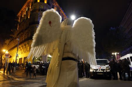 A demonstrator dressed as an angel faces French riot police officers during a rally in Marseille, October 31, 2014. REUTERS/Jean-Paul Pelissier