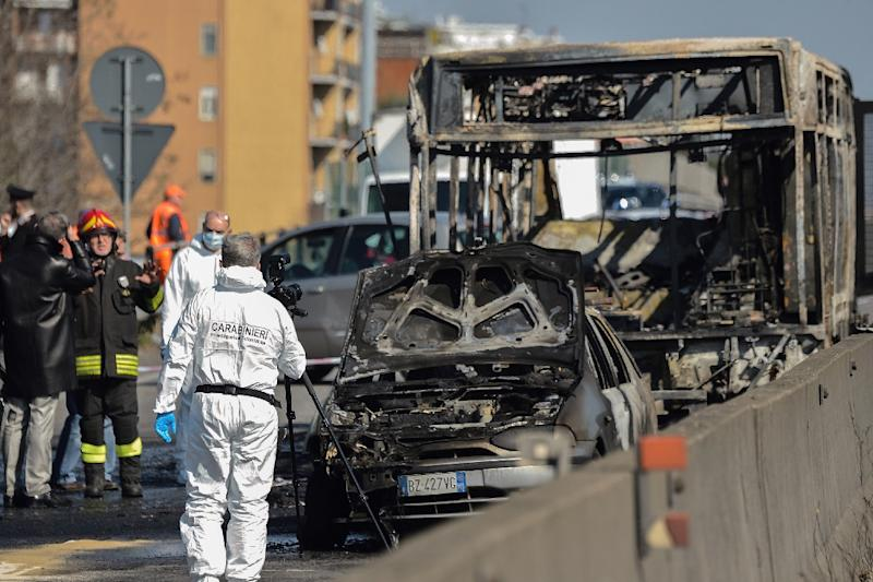 Forensic policemen and firefighters work near the wreckage of a school bus after rescuing some 50 children as the driver torched the vehicle, southeast of Milan
