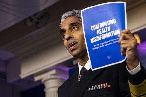 PHOTO: Vivek Murthy, U.S. surgeon general, displays a leaflet titles 'Confronting Health Misinformation as he speaks during a news conference  in Washington, July 15, 2021. (Bloomberg via Getty Images)