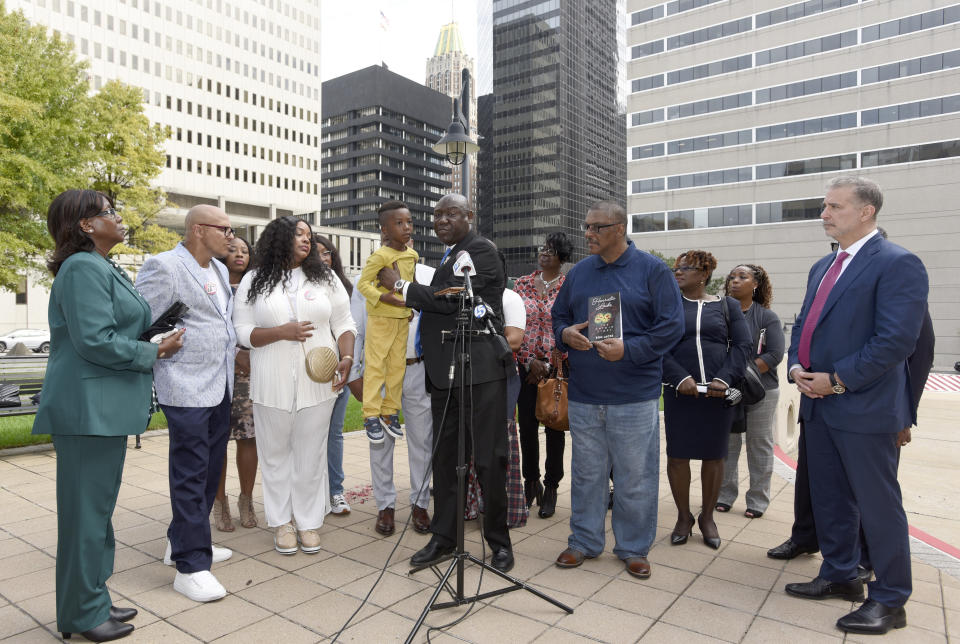 Attorney Ben Crump, center, holds Zayden Joseph, 6, the great-grandson of Henrietta Lacks, while standing with attorneys and other descendants of Lacks, whose cells have been used in medical research without her permission, outside the federal courthouse in Baltimore, Monday, Oct. 4, 2021. They announced during a news conference that Lacks' estate is filing a lawsuit against Thermo Fisher Scientific for using Lacks' cells, known as HeLa cells. (AP Photo/Steve Ruark)
