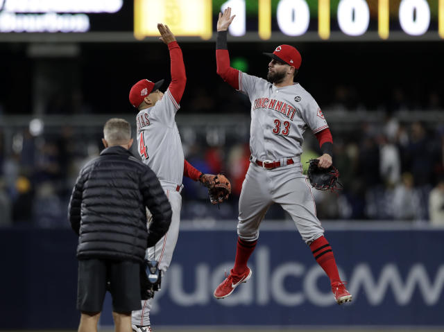 Cincinnati Reds center fielder Jesse Winker (33) and shortstop Jose Iglesias (4) celebrate after defeating the San Diego Padres 3-2 in a baseball game Friday, April 19, 2019, in San Diego. (AP Photo/Gregory Bull)