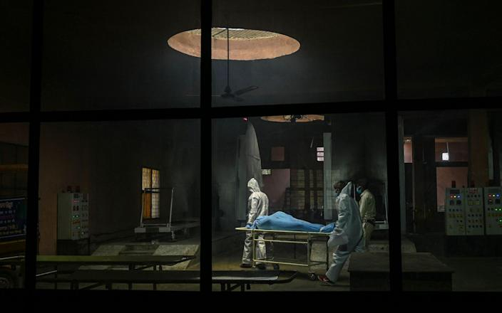 Ambulance staff wearing personal protective equipment suits carry the dead body of a person, who died due to the coronavirus, inside a crematorium - Prakash SINGH / AFP