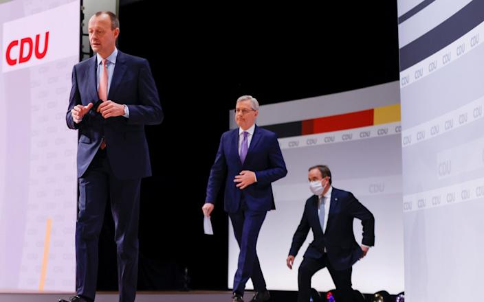 The three candidates for the leader of the Christian Democratic Union (CDU) Friedrich Merz, Norbert Roettgen and North Rhine-Westphalia's State Premier Armin Laschet arrive on stage to take questions from the delegates during the second day of the party's 33rd congress held online amidst the coronavirus disease (COVID-19) pandemic, in Berlin, Germany January 16, 2021. Odd Andersen/Pool via REUTERS - POOL/REUTERS